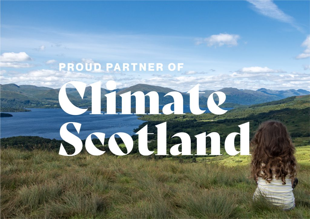 """A young girl looks out over a landscape of lochs and mountains, under a blue sky.  The words """"Proud Partner of Climate Scotland"""" are overprinted."""